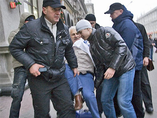 Photo of leather-jacketed police arresting a protester